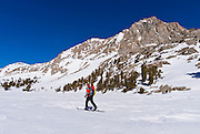 Backcountry skier crossing Loch Leven under Piute Pass, Inyo National Forest, Sierra Nevada Mountains, California
