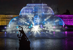 © Licensed to London News Pictures. 21/11/2017. London, UK. Images of snow flakes projected onto water vapour in front of the Palm House herald the opening of Christmas at Kew at Royal Botanical Gardens, Kew. The spectacular displays are illuminated by over one million tiny twinkling lights placed all over Kew Gardens - open Wednesdays – Sundays from 22 November 2017 – 2 January 2017. London, UK. Photo credit: Peter Macdiarmid/LNP