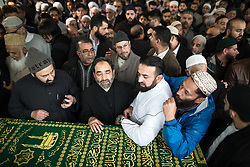 © Licensed to London News Pictures . 12/05/2017 . Manchester , UK . Family around the coffin , at the service . Thousands of people fill a mosque , inside a marquee at the British Muslim Heritage Centre in Whalley Range , Manchester , for the funeral of Mawlana Habib-ur-Rahman , at the British Muslim Heritage Centre , Whalley Range , Manchester . Rahman , a former maths teacher and then imam at Manchester Central Mosque , died aged 90 following heart problems . As a well-known leader of Manchester's Muslim community he promoted interfaith dialogue and met the Pope during a Papal visit to Manchester in 1982 . Due to the number attending , crowds attending the funeral had to be diverted to rooms in nearby buildings to listen to the service via loudspeaker . Photo credit : Joel Goodman/LNP