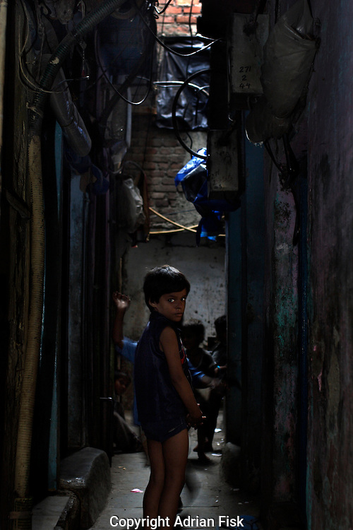 A young boy looks back within the narrow alleys of Dharavi on 21st Oct 2006. Dharavi is made up of a maze of alleyways, such is the shortage of space most are not much wider than a man.