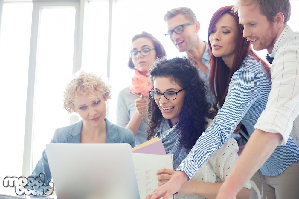 Group of creative businesspeople using laptop in office