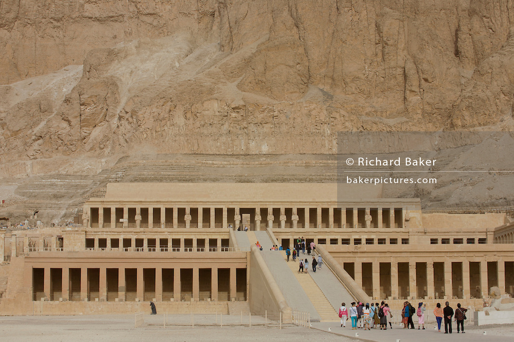 """Tourists approach the ancient Egyptian Temple of Hatshepsut near the Valley of the Kings, Luxor, Nile Valley, Egypt. The Mortuary Temple of Queen Hatshepsut, the Djeser-Djeseru, is located beneath cliffs at Deir el Bahari (""""the Northern Monastery""""). The mortuary temple is dedicated to the sun god Amon-Ra and is considered one of the """"incomparable monuments of ancient Egypt."""" The temple was the site of the massacre of 62 people, mostly tourists, by Islamists on 17 November 1997."""