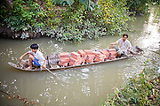 11 MARCH 2006 - CAI BE, TIEN GIANG, VIETNAM: Men paddle a canoe of tiles up a canal in Cai Be in the Mekong River delta in Vietnam. The Mekong is the lifeblood of southern Vietnam. It is the country's rice bowl and has enabled Vietnam to become the second leading rice exporting country in the world (after Thailand). The Mekong delta also carries commercial and passenger traffic throughout the region.  Photo by Jack Kurtz