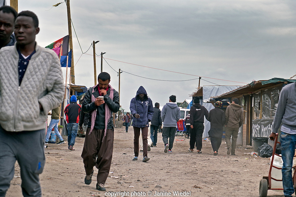 The main entrance lined with makeshift pop-up shops selling basic needs. The Calais Jungle Refugee and Migrant Camp in France
