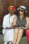 Touristin l?sst sich in der Altstadt von Havanna / Kuba mit Zigarre rauchender einheimischen alten Dame in traditioneller Tracht fotografieren