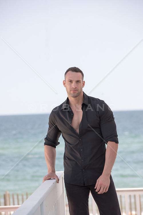 hot man on a deck overlooking the ocean