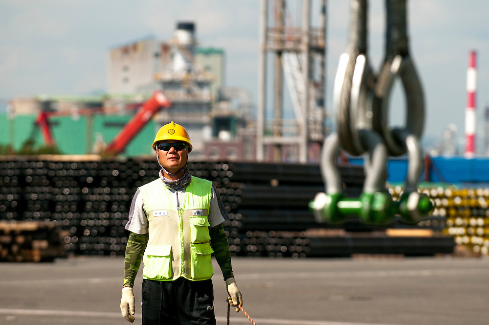 A worker watches cargo lift operations at Ulsan Port, Ulsan, South Korea.