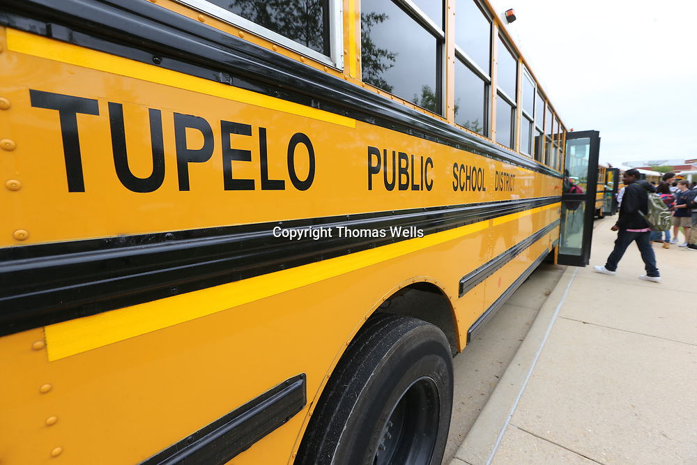 Students at Tupelo High School board their buses after school on Monday.