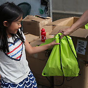 August 16, 2014, New Haven, CT:<br /> A volunteer gives a young fan an AETNA goody bag as she enters the grounds during Kids Day on day three of the 2014 Connecticut Open at the Yale University Tennis Center in New Haven, Connecticut Sunday, August 17, 2014.<br /> (Photo by Billie Weiss/Connecticut Open)