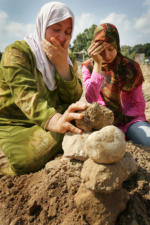 29th July 2006&#xD;&#xA;Tyre, Lebanon&#xD;&#xA;Mass Burial.&#xD;&#xA;&#xD;&#xA;Amina Baalbeki (left to right) and her daughter Nazeera Kassab, grieve at the site of a mass burial of more than 30 people killed by Israeli bombardment. Aminas mother Nazerra Birro was amoungst those interned.<br />