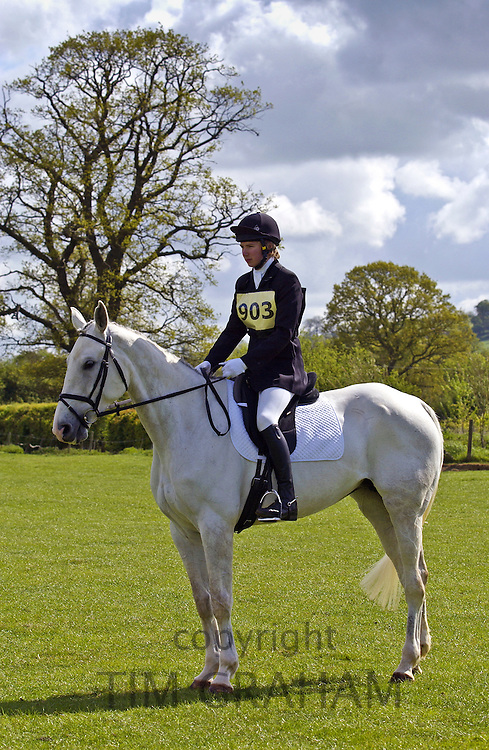 Young man on grey mare horse prepares to ride dressage at eventing competition, Oxfordshire, United Kingdom