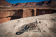 Riders take in the expansive views into the canyon on  mountain bikes while touring the White Rim Trail near Moab, Utah.