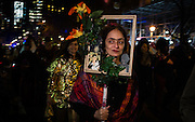New York, NY - 31 October 2016. A woman costumed as Mexican artist Frida Kahlo, with her face behind a frame.