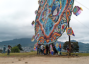 A group posing for a picture is dwarfed by the size of the giant kite.