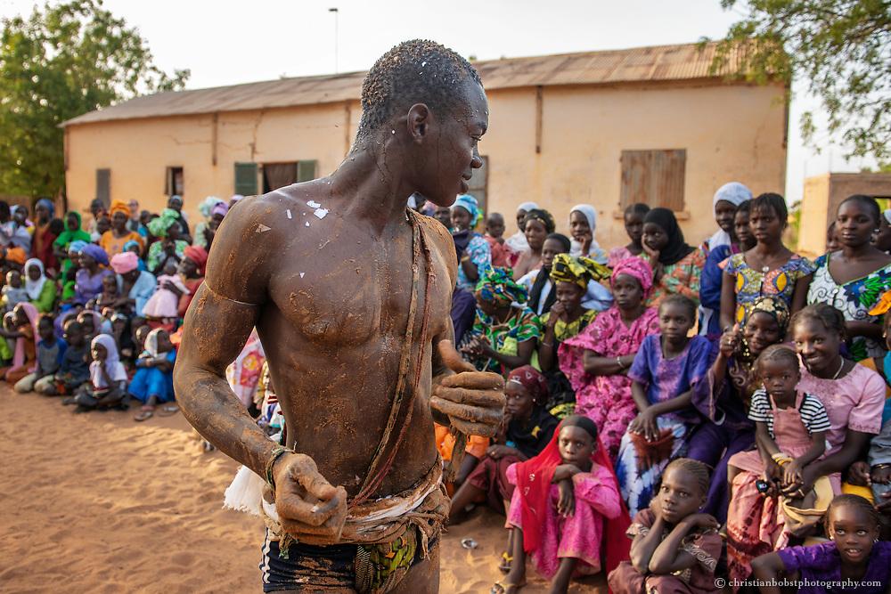 Ein Ringer lächelt bei einem Ringkampf im Dorf Soune in der Nähe von Thies einem Mädchen im Publikum zu. Das senegalesische Wrestling ist ein Volkssport, welcher auch in den kleinsten Dörfern ausgetragen wird.