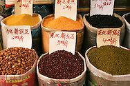 Various grains, nuts and beans at a Chengdu Market, displayed with prices per kilo in burlap and plastic bags.