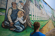 Girl walks into outdoor mural in author Harper Lee's hometown depicting Scout, Jem and Dill hiding behind tree to spy on Boo Radley in scene from To Kill a Mockingbird; Monroeville, Alabama.