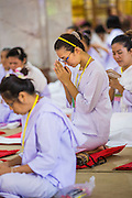 11 JULY 2014 - BANGKOK, THAILAND:  Women pray at Wat Pathum Wanaram for Asalha Puja Day. Asalha Puja is the day the Lord Buddha preached his first sermon to followers after attaining enlightenment. The day is usually celebrated by merit making and listening to a monks' sermons. It is also day before the start of the Rains Retreat, the three month period when monks stay in their temple for intense mediation and spiritual renewal.   PHOTO BY JACK KURTZ