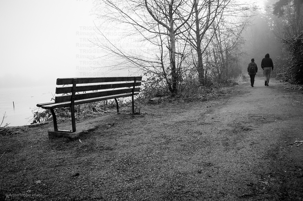 A couple walking down a nature trail with a park bench in the foreground and fog in the distance.