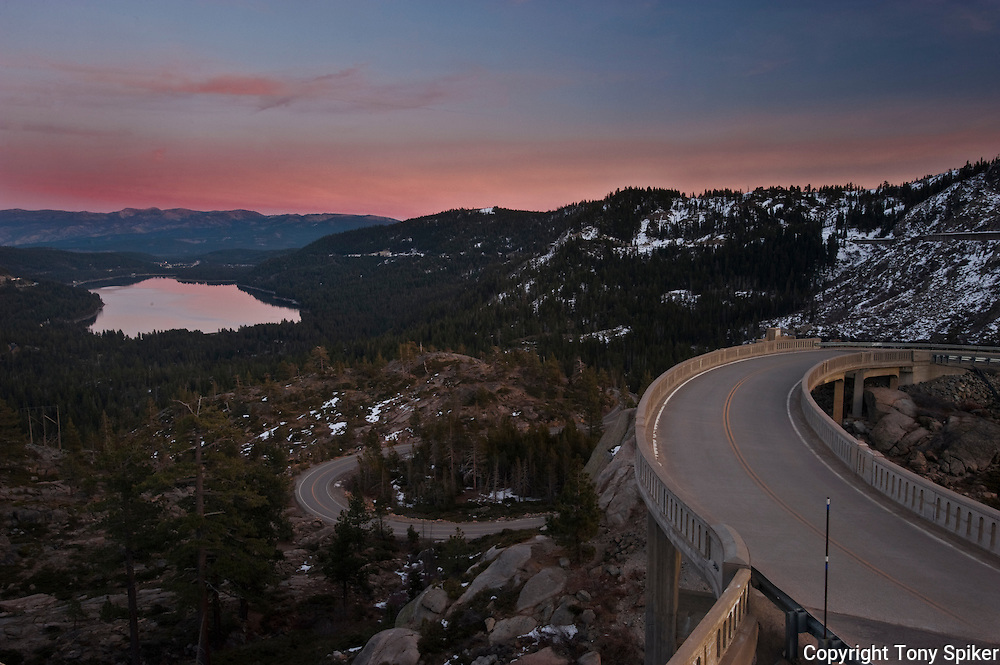 """Donner Lake Sunset 1"" - A photograph of the sun setting over Donner Lake with Rainbow Bridge in the foreground."