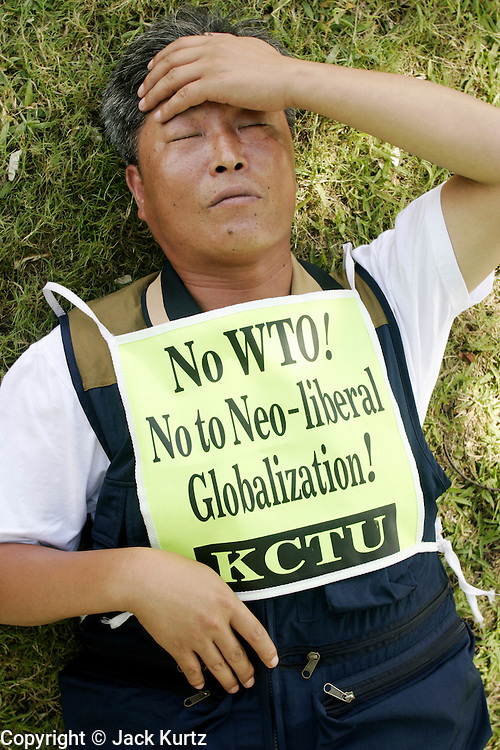 12 SEPTEMBER 2003 - CANCUN, QUINTANA ROO, MEXICO: A Korean anti-WTO protestor sleeps in a park in Cancun, Mexico during a break in the protests against the WTO Friday. The Koreans have emerged as the most determined and vocal anti-WTO protestors. Lee Kyung-hae, one of the Korean protestors, killed himself after unfurling an anti-WTO banner during a protest against the trade organization. Thousands of anti-globalization protestors have come to Cancun to try to disrupt the 5th Ministerial meeting of the World Trade Organization. The protestors have been restricted to downtown Cancun, while the WTO is meeting 10 miles away in the Cancun tourist zone. PHOTO BY JACK KURTZ