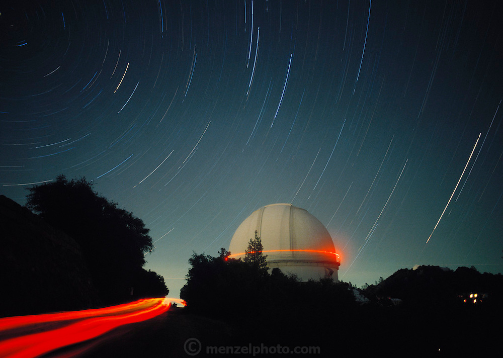 Lick Observatory. Time exposure image showing star trails over a telescope dome at the Lick Observatory on Mount Hamilton in California, USA. In the foreground are trails from red taillights of a car. Astronomers often carry red flashlights so that their night vision is not affected. Completed in 1888 at an altitude of 1280 meters, Lick was the world's first permanent mountaintop observatory. Its location provided excellent viewing conditions for years until light pollution from the nearby city of San Jose began to interfere with results. In 1997 the observatory is operated by California University. Star trails are caused by what seems to be the motion of the stars due to the rotation of the Earth about its axis.