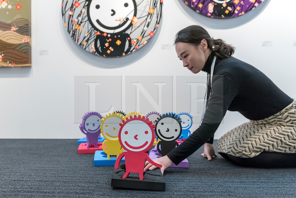 © Licensed to London News Pictures. 16/01/2018. LONDON, UK. A staff member makes adjustments to foam works by Korean artist Kisoo Kwon. Preview day of the 30th anniversary of the London Art Fair.  The fair launches the international art calendar with modern and contemporary art from leading galleries around the world and is taking place at the Business Design Centre, Islington from 17 to 21 January 2018.   Photo credit: Stephen Chung/LNP