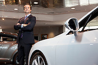 Confident car salesperson standing with arms crossed