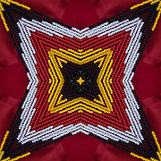 Computer enhanced kaleidoscope of  red, white, yellow, black color beads  zooming to center point.