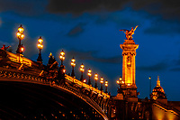 Pont Alexandre III (bridge) across the Seine River with Hotel des Invalides behind. The bridge is the most ornate in the city and features art nouveau lamps, cherubs, nymphs and on the two large gilded sculptures at the end, winged horses. Paris, France.
