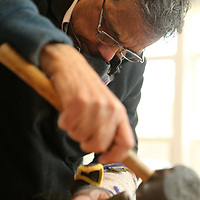 Gupta lightly taps a wood chisel with a rubber mallet to smooth the edges on his large spatula.