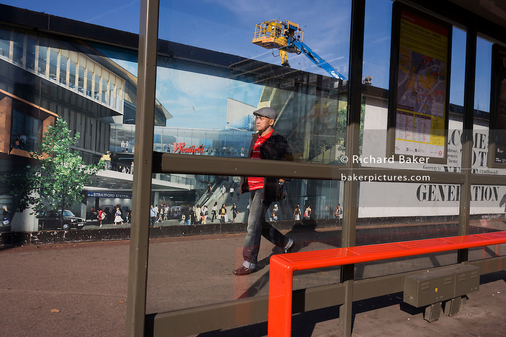 Local man passes a hoarding showing aspiration and consumerism of nearby Westfield City shopping complex, Stratford