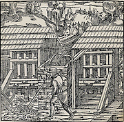 Stamping mills powered by and overshot water wheel being used to crush ore to begin the process of extracting metal from the ore won from a mine.   From 'De re metallica', by Agricola, pseudonym of Georg Bauer (Basle, 1556).  Woodcut.  Mining. Metal. Power. Water.