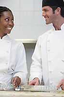 Two chefs preparing food in kitchen smiling
