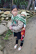 Hilltribe villages around Sapa. Black Hmong girl with baby child on her back.