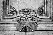 A bronze lion head embellishes a carved wooden door of an apartment building in Paris.