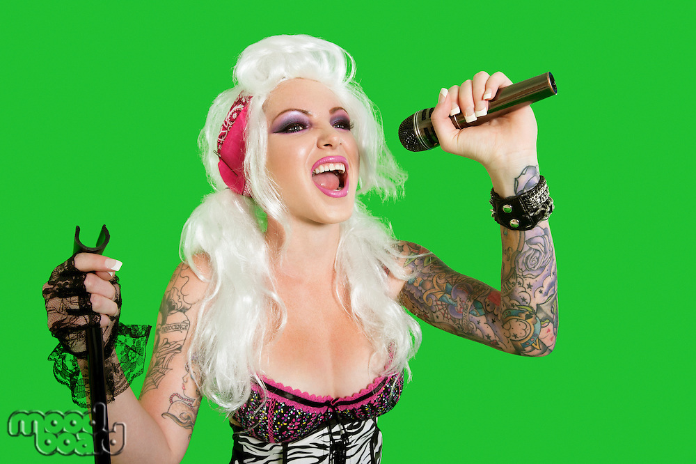 Beautiful tattooed woman singing with microphone over green background