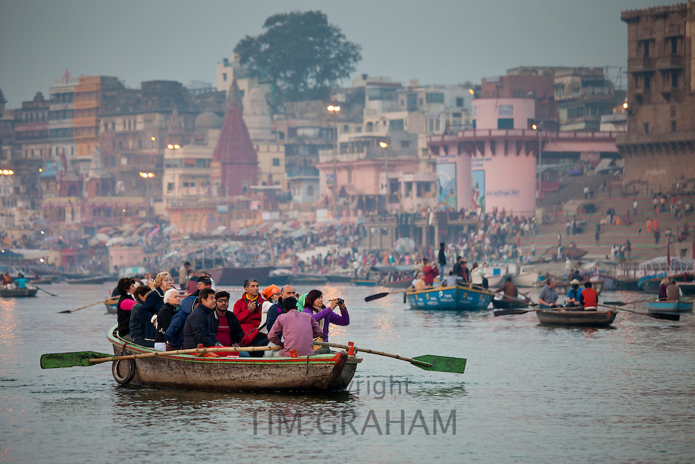 Traditional scenes of tourists in boats on River Ganges at Varanasi, Benares, Northern India
