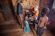 Mforo, Tanzania a village near Moshi, Tanzania.<br /> Solar Sister entrepreneur Fatma Mziray, age 38 delivers a clean wood cookstove to Ester Hodari, age 22. Ester had been continually getting sick with a chest cough and red eyes. Often when she is cooking her three children are with her in the kitchen hut breathing in the smoke that is produced from the wood fire. Ester and her husband decided to purchase a clean cookstove from Fatma after their 3-month-old baby developed a cough and they had to rush her to the hospital. When Fatma demonstrated the new stove to Ester she saw that it used less wood and produced almost no smoke. Ester met Fatma when she married her husband and she moved to this village. She said Fatma is like a mother in the village and everyone knows and likes her.   Ester&rsquo;s daughter Fadhila Marijani, 2 years old, and her son Abuu Marijani, 5 re in some of the pictures.<br /> Fatma Mziray is a Solar Sister entrepreneur who sells both clean cookstoves and solar lanterns. Fatma heard about the cookstoves from a Solar Sister development associate and decided to try one out. The smoke from cooking on her traditional wood stove using firewood was causing her to have a lot of heath problems, her lungs congested her eyes stinging and her doctor told her that she had to stop cooking that way. Some days she felt so bad she couldn't go in to cook. Fatma said, &ldquo;Cooking for a family, preparing breakfast, lunch and dinner I used to gather a large load of wood every day to use. Now with the new cook stove the same load of wood can last up to three weeks of cooking. <br /> <br /> &ldquo;With the extra time I can develop my business. I also have more time for the family. I can monitor my children&rsquo;s studies. All of this makes for a happier family and a better relationship with my husband. Since using the clean cookstove no one has been sick or gone to the hospital due to flu.&rdquo;  Fatma sees herself helping her community because she no longer se