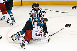 Jan 31, 2012; San Jose, CA, USA; San Jose Sharks defenseman Colin White (5) knocks Columbus Blue Jackets right wing Derek Dorsett (15) to the ice in a fight in front of NHL linesman Pierre Champoux (67) during the third period at HP Pavilion. San Jose defeated Columbus 6-0. Mandatory Credit: Jason O. Watson-US PRESSWIRE