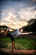 A yogi does Dandayamana Dhanurasana (standing bow pose) in front of a rice field at sunset.