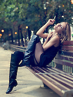 Beautiful sexy blonde woman in a miniskirt and long boots posing on a park bench looking at the camera while smoking a cigarette