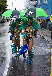 London, August 31st 2015. Two women make their way towards their troupe as revellers ignore the inclement weather to enjoy day two of the Notting Hill Carnival.