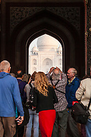 Looking through the main entrance gate at The Taj Mahal in Agra, India with tourists taking pictures in the foreground.