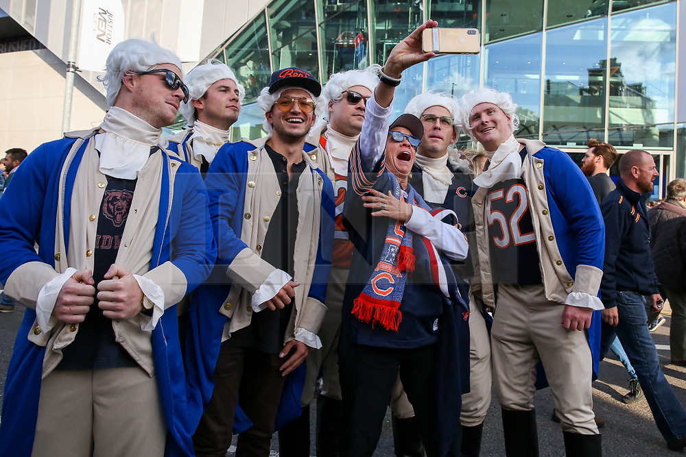 © Licensed to London News Pictures. 06/10/2019. London, UK. American Football fans dressed as Benjamin Franklin (Founding Father of the United States) takes a selfie as fans arrive for the NFL (The National Football League) London Games when Oakland Raiders faces Chicago Bears in the first of the two games to be played at the new Tottenham Hotspur Stadium. Photo credit: Dinendra Haria/LNP