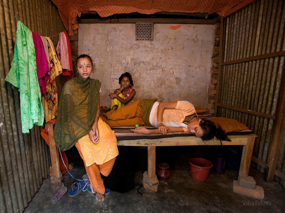 Sex worker Nodi,14, left, sits with her cousin Suma, 8, background, whose mother is a sex worker, as her sister, also a sex worker, Shetu, 17, foreground, sleep at brothel in Tangail, Bangladesh. Nodi run away from home after falling in love with a Hindu boy and ended up in the brothel with her sister at the brothel.