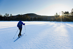 A man cross-country skiing on a frozen pond near Little Lyford Pond Camps near Greenville, Maine, Winter.