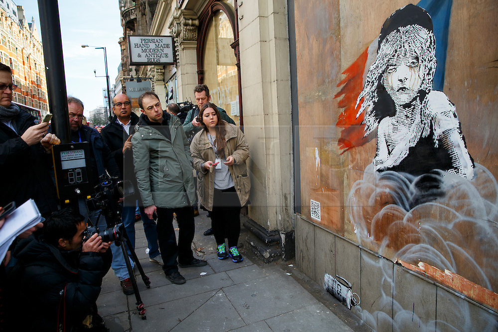 © Licensed to London News Pictures. 25/01/2016. London, UK. Members of public looking at a new Banksy mural criticising the use of teargas on refugees in Calais has appeared on a building opposite the French Embassy in London on Monday, 25 January 2016. Photo credit: Tolga Akmen/LNP