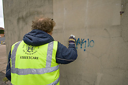 Council worker chemically removing graffiti off wall Havering London UK