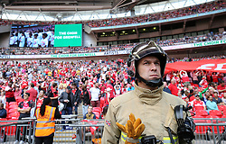 A fireman stands with the crowd as The Choir For Grenfell sings before the game
